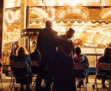 a couple standing and watching the carousel