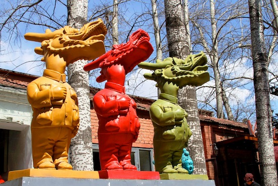 """""""Three Little Dragons"""" each holding Mao's Little Red Book."""