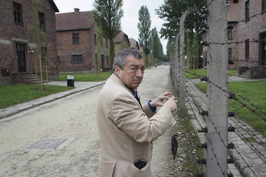 Philippe Mora stands next to one of the camp's infamous barbed wire fences.
