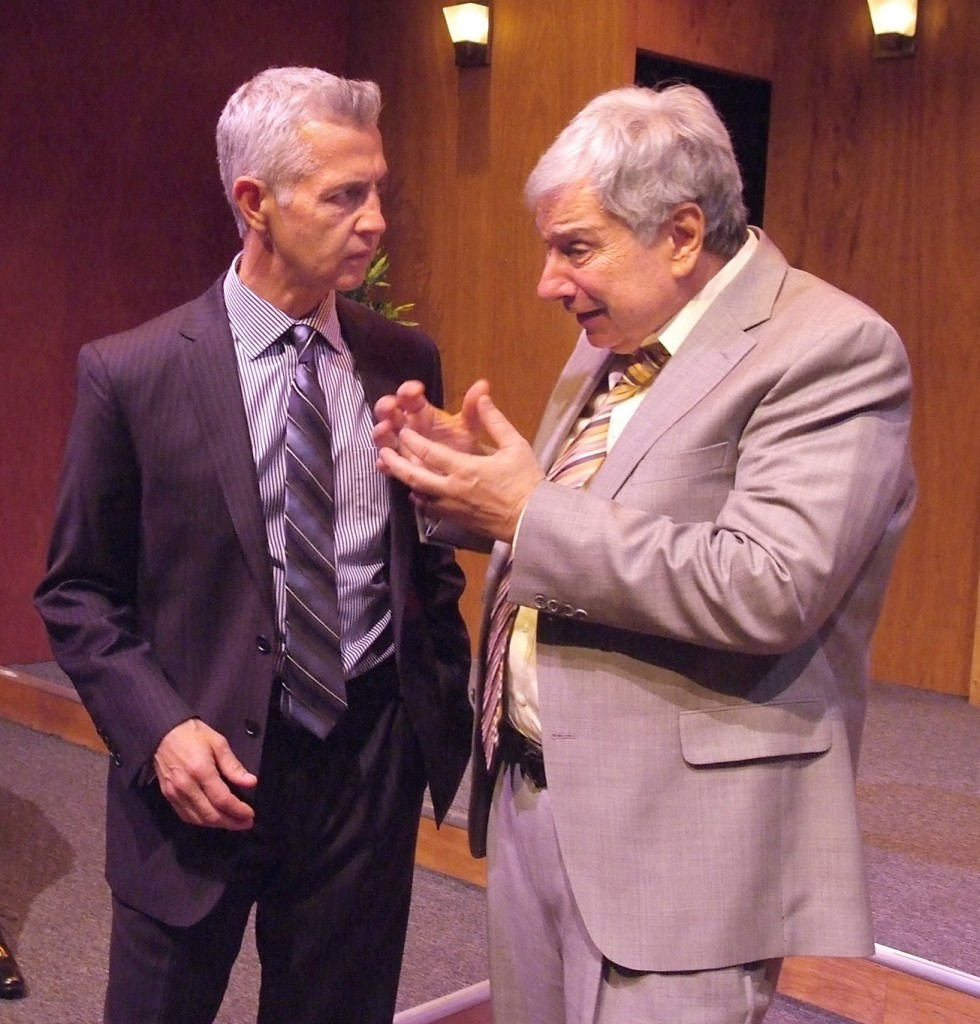 two men in suits, one light, one dark, gray hair, in intense conversation