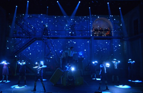 blue lit stage with a group of people each holding white lights