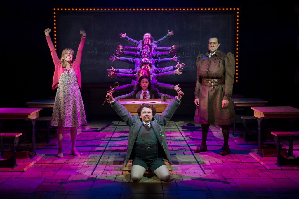 """Jennifer Blood (L), Evan Gray (front center), Bryce Ryness (R), Gabby Gutierrez (center middle) and the Company of Matilda The Musical National Tour. Based on the beloved novel by best-selling author Roald Dahl, ""Matilda The Musical"" has a book by Dennis Kelly, music and lyrics by Tim Minchin and is directed by Matthew Warchus. ""Matilda The Musical"" will be presented May 29 – July 12, 2015, at the Center Theatre Group/Ahmanson Theatre. For tickets and information, please visit CenterTheatreGroup.org or call (213) 972-4400. Contact: CTGMedia@CenterTheatreGroup.org / (213) 972-7376 Photo by Joan Marcus """