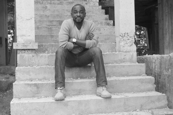 black and white photo of a young black male sitting on steps