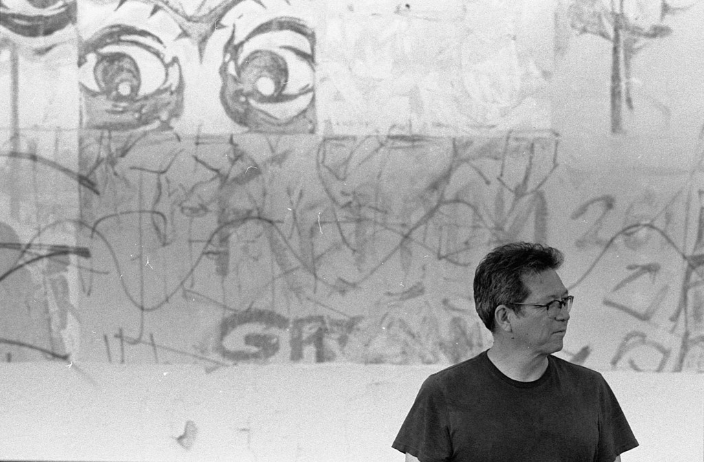 sesshu foster standing in a black t-shirt in front of a vandalized wall