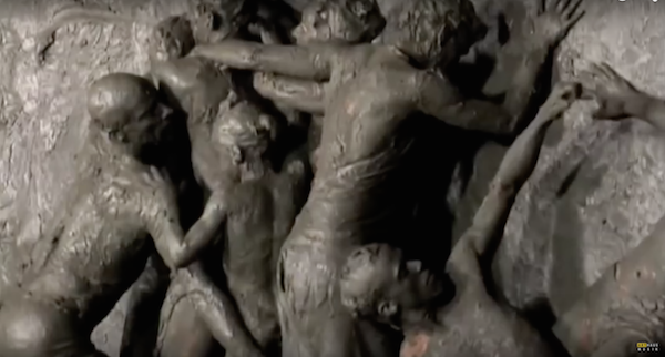 Mud covered dancers writhe on a wall in performance
