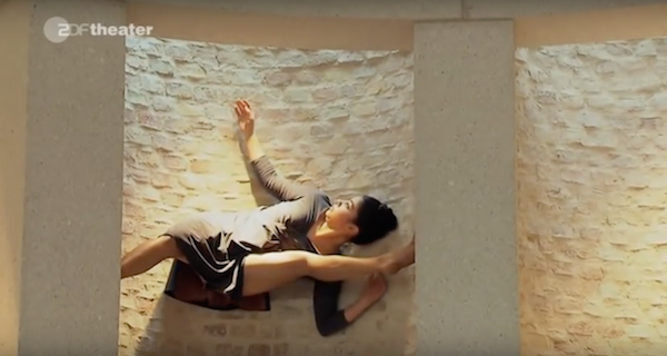 A dancer scales a wall of the Neues Museum