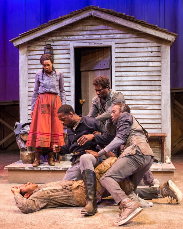"L-R: Sameerah Luqmaan-Harris (standing), Larry Powell, Sterling K. Brown, Russell G. Jones and Julian Rozzell Jr. in ""Father Comes Home From The Wars (Parts 1, 2 & 3)"" at Center Theatre Group/Mark Taper Forum. Written by Suzan-Lori Parks and directed by Jo Bonney, the West Coast premiere of ""Father Comes Home From The Wars (Parts 1, 2 & 3)"" plays April 5 – May 15, 2016. For tickets and information, please visit CenterTheatreGroup.org or call (213) 628-2772.  Contact:  CTG Media and Communications/ (213) 972-7376/CTGMedia@ctgla.org Photo by Craig Schwartz."