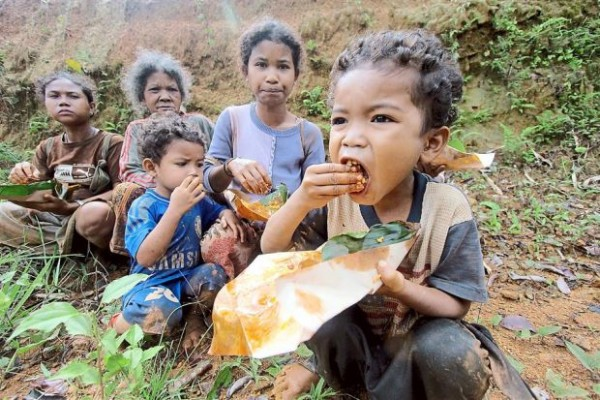 Orang Asli children having food after a helicopter delivered supplies near their village during the flood. -Photo by Bernama