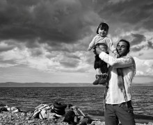 Refugees, Greece © Tom Stoddart   A father celebrates his family's safe passage to Lesbos after a stormy crossing over the Aegean Sea from Turkey.