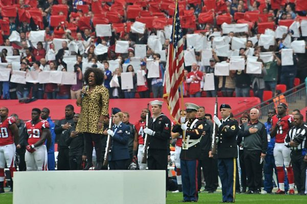 Jazz singer Dianna Reeves sings the U.S. National Anthem as the RAF Molesworth, United Kingdom color guard presents the U.S. flag during the NFL game at Wembly Stadium in London, England Oct. 26, 2014. Every year, London hosts three games as part of the NFL International Series. (U.S. Air Force photo by Staff Sgt. Ashley Hawkins/Released)