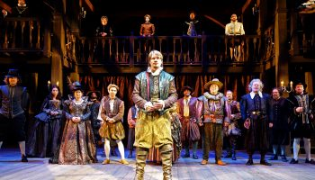 Paul David Story as Will Shakespeare center stage with the cast of Shakespeare In Love behind him at South Coast Repertory. Photo by