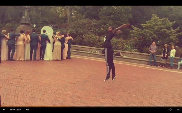 A dancer mid-air during a wedding party photo at Bethesda Fountain