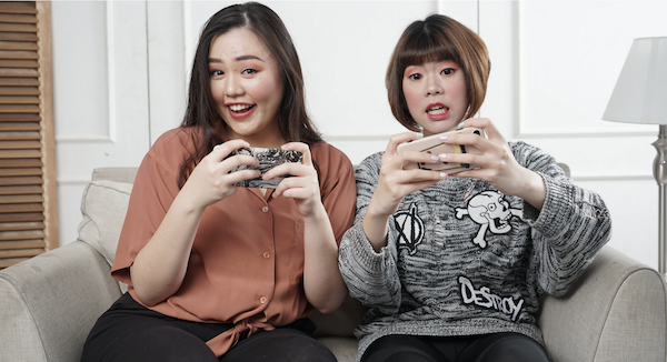 Two women playing social games. Photo by Afif Kusama via Unsplash.