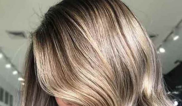Dirty blonde hair with black roots.