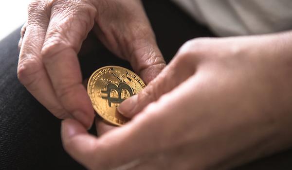 Holding a Bitcoin. Photo by André François McKenzie via Unsplash.