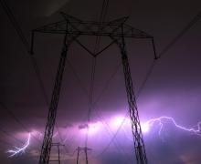 Transmission lines and lightning. Photo by Casey Horner via Unsplash,