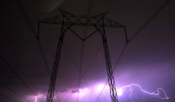 Transmission lines and lightning. Photo by Casey Horner via Unsplash,