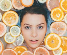 Woman surrounded by citrus. Photo by Noah Buscher via Unsplash.