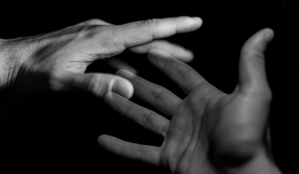 Two hands. Photo by Marco Chilese via Unsplash.