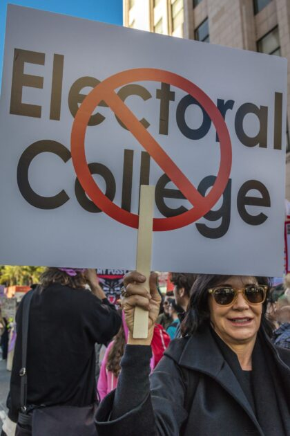 Demonstrator at the 2017 Women's March holds a sign protesting for electoral college reform