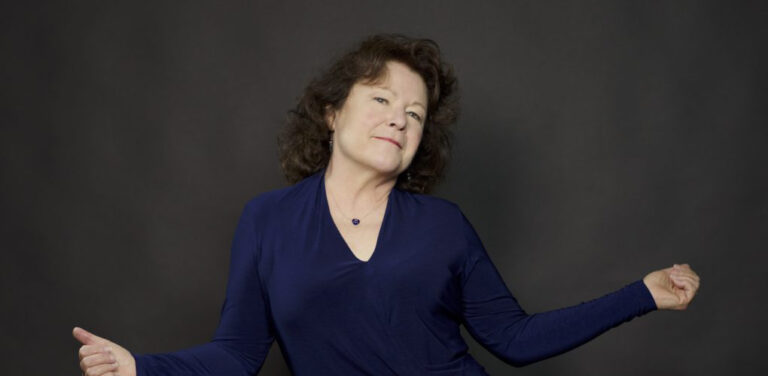 Photo of Beth Ruscio, a Caucasian woman, looking at the camera with her arms spread out, in front of a dark background.