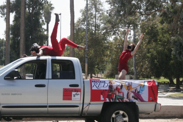 Two people in red outfits dancing on top of a gray pickup truck parked.
