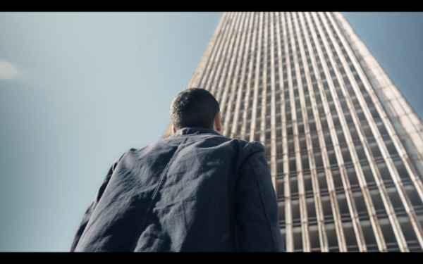 A low angle shot of the back of a man, standing in front of a high-rise, looking up.