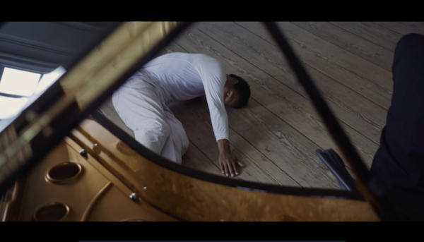 A man wearing white writhes on the floor in front of a piano.