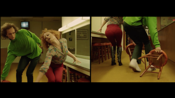 A split screen shot of a couple of dancers, one front view and one back view, dancing synchronized. He is wearing  green long sleeve top and black pants. She is wearing a beige blouse and red pants. They're both dragging stools.