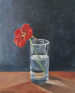 One of two collaborations. A painting of a red flower in a clear glass half filled with water. It is on a brown desk top in front of a blue wall.