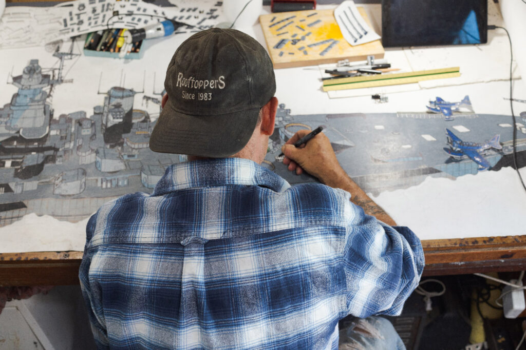 Back view of artist JD Smith sitting and painting. He is wearing a blue and white flannel shirt with a baseball cap worn backwards.