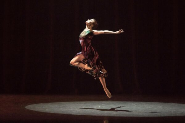 A dancer in a spotlight with her arms spread out and back, jumping in the air with one leg bent at the knee, her head tilted back.