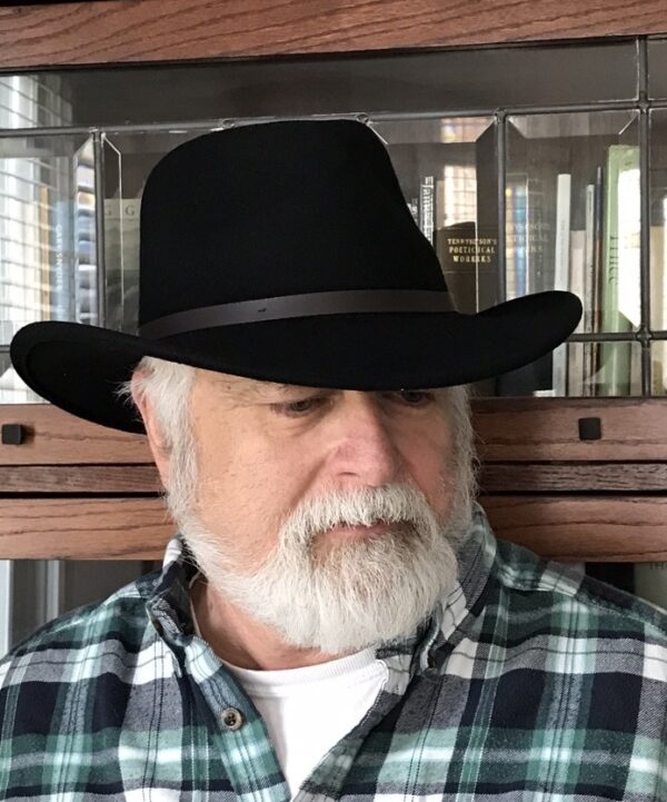 Image of the poet Michael Simms wearing a black cowboy hat and a blue and green flannel shirt. He is in front of a bookcase, looking off to his left.