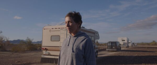 A screenshot of actress Frances McDormand standing in front of a RV, parked on the side of the road under a blue sky, from the film Nomadland.