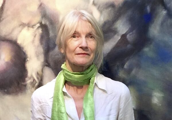 Image of poet Rachel Hadas looking into the camera, wearing a white top and a lime green scarf. She is standing in front of a painting.