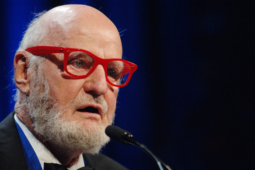 A photo of Lawrence Ferlinghetti at a microphone, wearing red rimmed glasses and a tuxedo.
