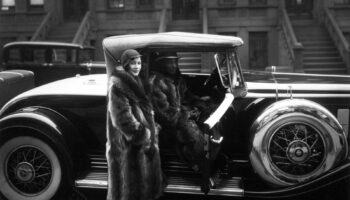 A black and white photo by James Van Der Zee of a well dressed Black woman standing next to a car, its door open, looking straight into the camera.