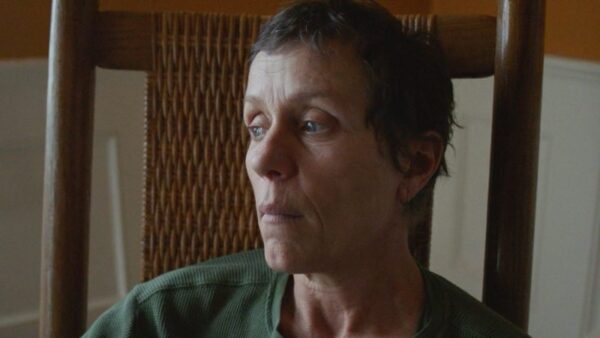 A medium shot of actress Frances McDormand wearing a green shirt, sitting on a wooden chair, from the film Nomadland.