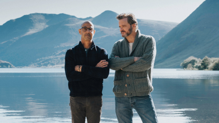 Two men stand next to each other with their arms crossed, with the blue water and the blue mountains behind them.